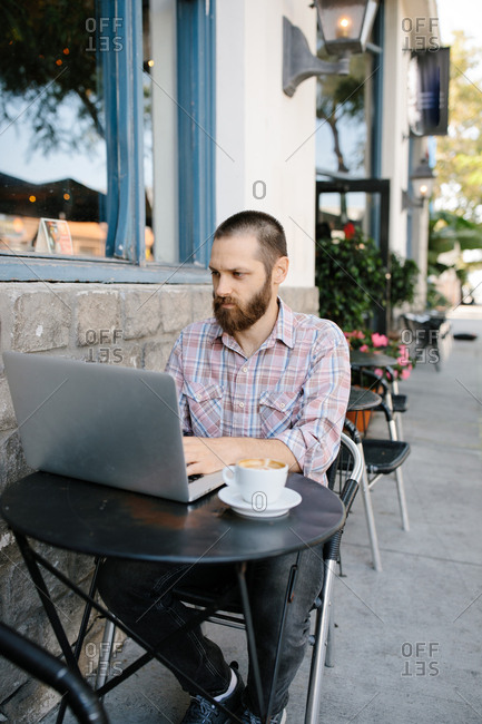 Young man working remotely from an outdoor coffee shop