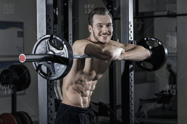 Shirtless muscular man leaning and relaxing on barbell while exercising at the gym