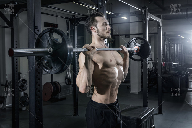 Shirtless muscular man exercising with barbell at the gym