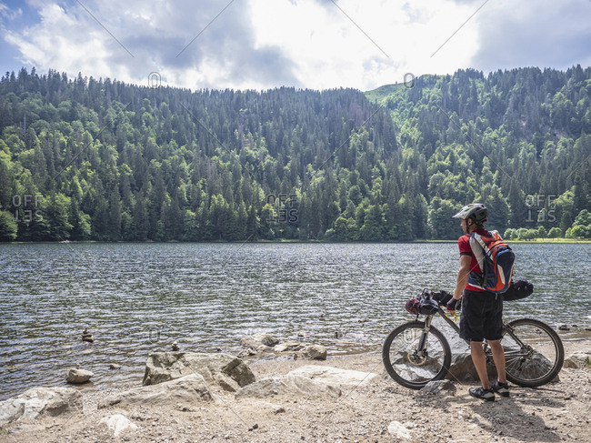 Mountain biker resting at lake Feldsee near Mt Feldberg, Baden-W�rttemberg, Germany