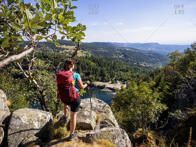 Rear view of women hiker looking at view of forest from Hans rock edge above Lac Blanc at Rocher Hans, France