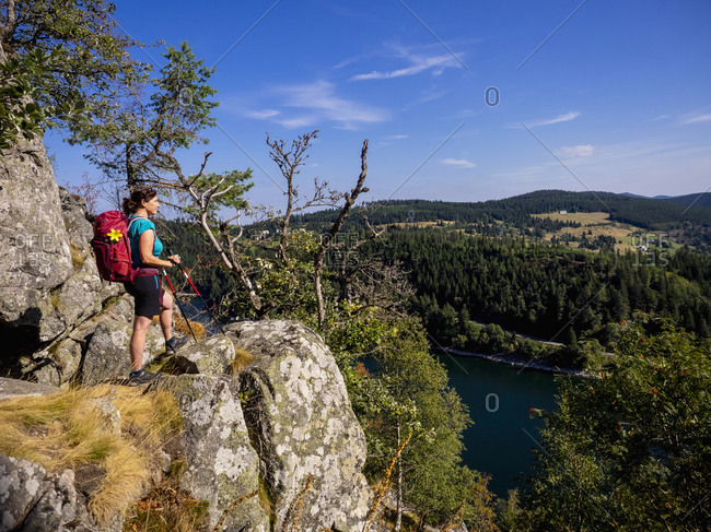 Women hiker looking at view of forest from Hans rock edge above Lac Blanc at Rocher Hans, France