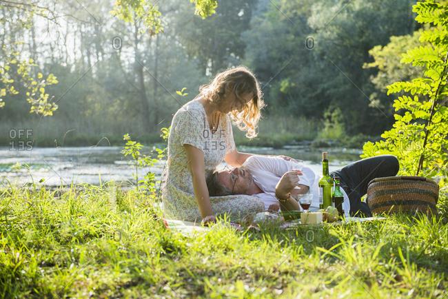 Romantic couple enjoying picnic by lake, Germany