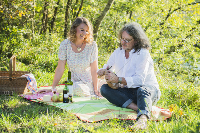Couple slicing bread on a picnic day near lakeshore, Germany, Bavaria