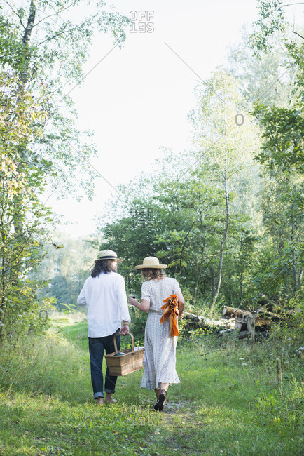 Rear view of couple walking with a picnic basket in park, Bavaria Germany
