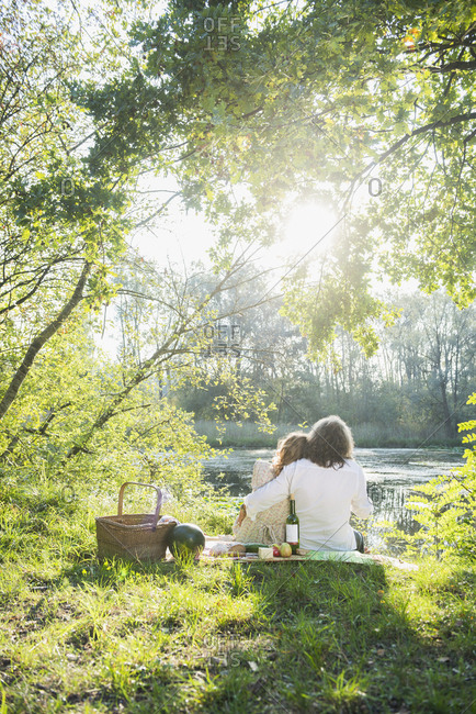 Rear view of romantic couple sitting near by lakeshore, Bavaria Germany