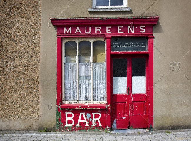Mallow, Ireland - May 30, 2019: Abandoned pub with red door