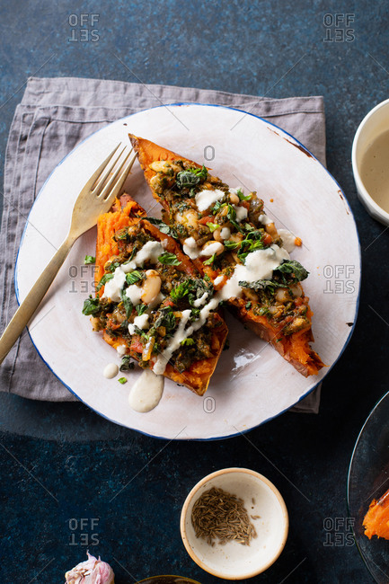 Overhead image of stuffed sweet potatoes with spinach, beans and tahini sauce