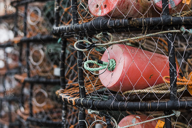 Crab and lobster pots stacked up on the quayside, close up.