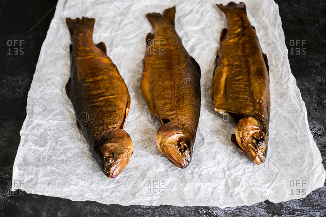 High angle close up of three freshly smoked whole trout on a white paper.