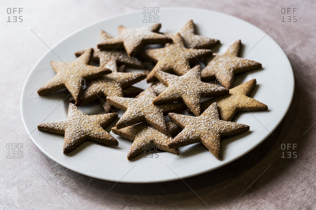 High angle close up of freshly baked star-shaped cookies dusted with icing sugar on a white plate.