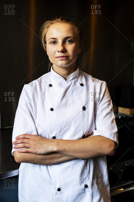 Woman wearing chef's jacket standing indoors with her arms folded, looking at camera.