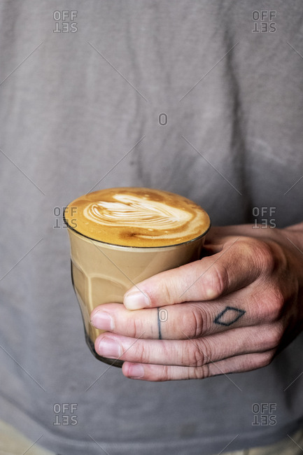 Close up of person with tattooed finger holding glass of cafe latte.