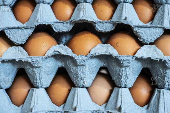 Full frame close up of a stack of blue cartons with brown eggs.