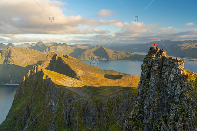 Man standing at the top of a pinnacle with a view over the landscape, Senja Island, Troms