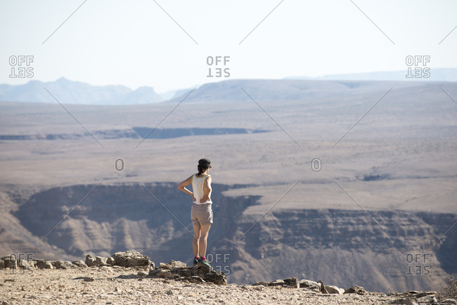A woman looks in the Fish River Canyon in Namibia from the beginning of the hiking trail