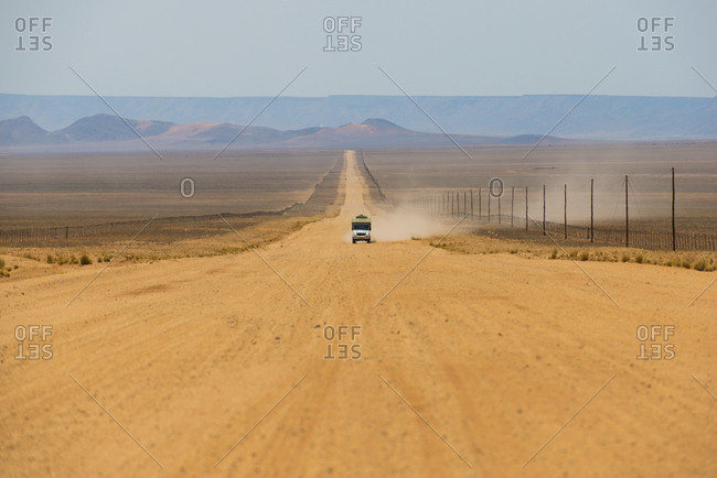 A vehicle driving on a long sandy road in southern Namibia leaves a trail of dust