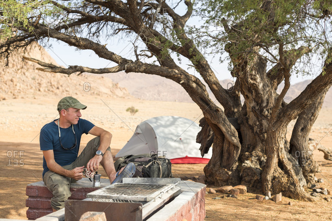 Man drinking coffee while camping on the edge of the Namib desert