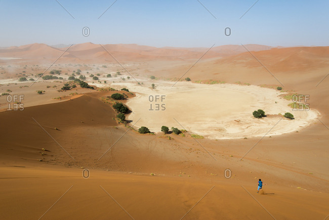 A woman runs down from the summit of Sossusvlei sand dune in Namibia
