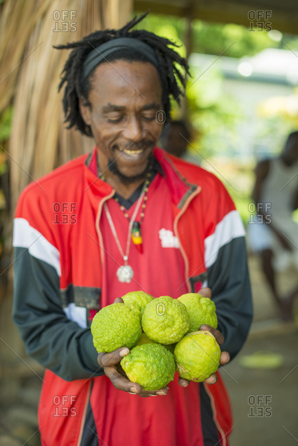 Castara, Tobago, Trinidad and Tobago - November 18, 2015: A man holds vibrant rough lemons at a fruit stall in Castara Bay on the Caribbean island of Tobago