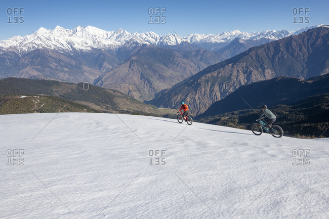 Mountain bikers descend a snow covered slope in the Himalayas with views of the Langtang range in the distance