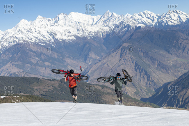 Gosainkund, Nepal - March 28, 2019: Mountain bikers carry their bikes up a snow covered slope in the Himalayas with views of the Langtang range in the distance
