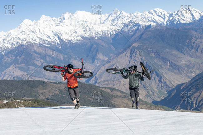 Gosainkund, Nepal - March 28, 2019: Mountain bikers carrying their bikes up a snow covered slope in the Himalayas with views of the Langtang range in the distance