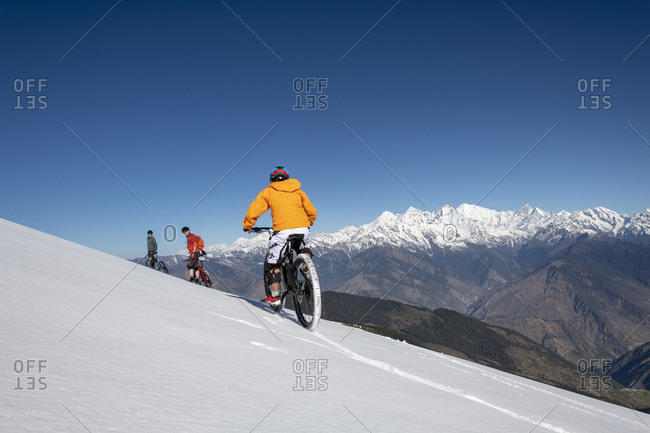 Gosainkund, Nepal - March 28, 2019: Three mountain bikers cycle along a snow covered slope in the Himalayas with views of the Langtang range in the distance