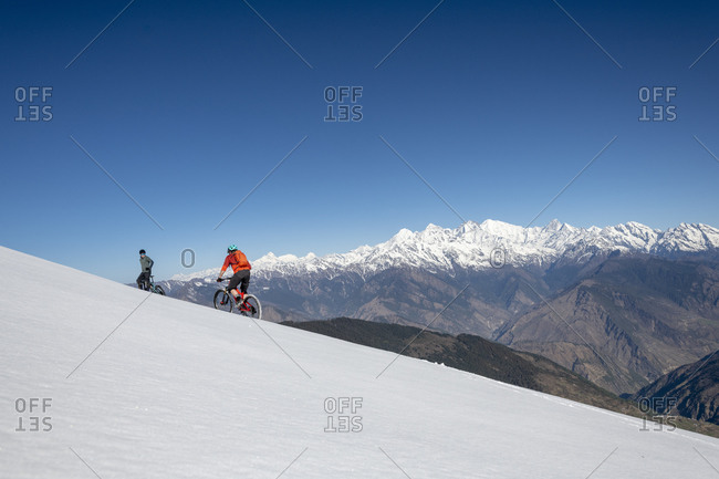 Mountain bikers cycle along a snow covered slope in the Himalayas with views of the Langtang range in the distance