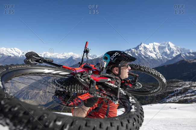 Gosainkund, Nepal - March 28, 2019: A mountain biker carries his bike up a snow covered hillside in the Himalayas with views of the Langtang mountain range in the distance