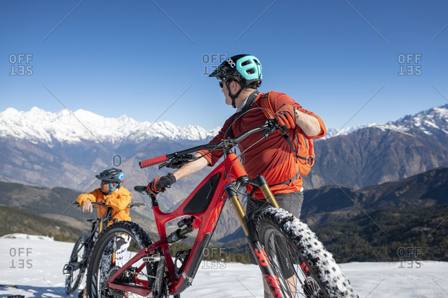 Gosainkund, Nepal - March 28, 2019: Mountain bikers taking in the view on a snow covered slope in the Himalayas with views of the Langtang range in the distance