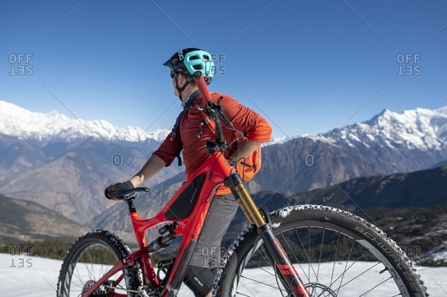 Gosainkund, Nepal - March 28, 2019: Mountain biker taking in the view on a snow covered slope in the Himalayas with views of the Langtang range in the distance