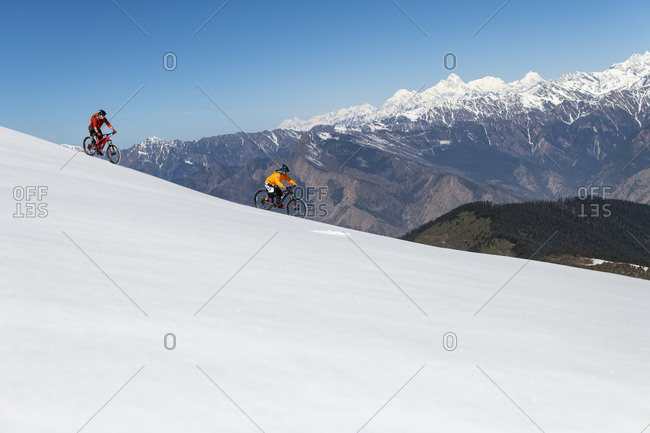 Gosainkund, Nepal - March 28, 2019: Mountain biking on a snow covered slope in the Himalayas with views of the Langtang mountain range