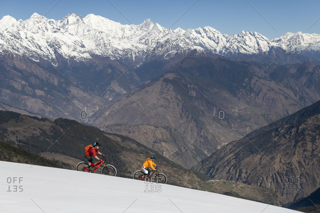 Mountain bikers on a snow covered slope in the Himalayas with views of the Langtang mountain range