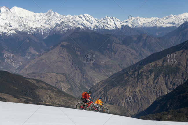 Gosainkund, Nepal - March 28, 2019: Men mountain biking on a snow covered slope in the Himalayas with views of the Langtang mountain range