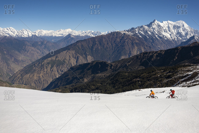 Two men mountain biking on a snow covered slope in the Himalayas with views of the Langtang mountain range in the distance