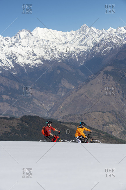 Gosainkund, Nepal - March 28, 2019: Two men mountain biking on a snow covered slope in the Himalayas with views of the Langtang mountain range