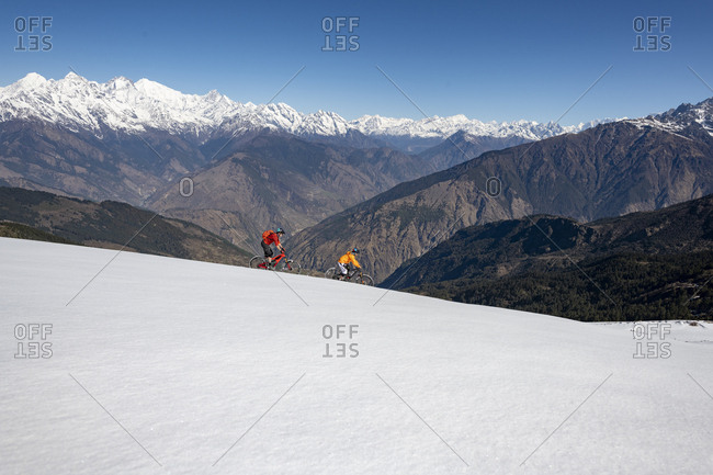 Gosainkund, Nepal - March 28, 2019: Mountain biking in the snow in the Himalayas with views of the Langtang mountain range in the distance