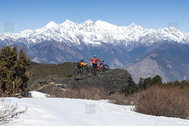 Gosainkund, Nepal - March 28, 2019: Mountain bikers taking in views of the Langtang range in the distance in the Himalayas