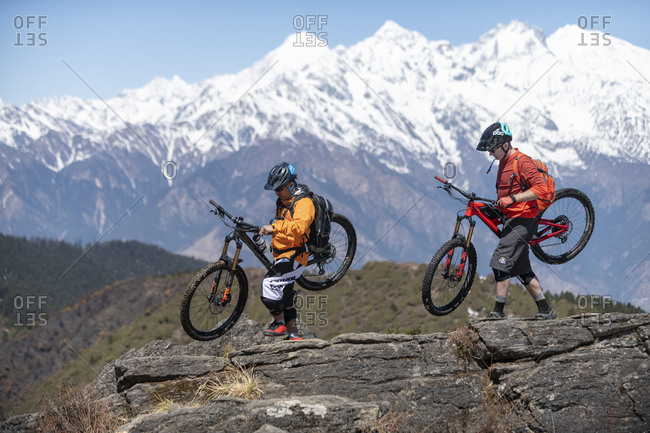 Gosainkund, Nepal - March 28, 2019: Two mountain bikers carrying bikes in the Himalayas with views of the Langtang range in the distance