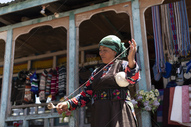 Gosainkund, Nepal - March 28, 2019: A Sherpa woman from Gosainkund spins baby Yak wool using the traditional method with a spindle