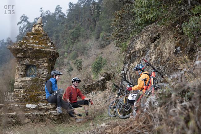 Gosainkund, Nepal - March 29, 2019: Mountain bikers take a break near a moss covered Tibetan chorten in the Himalayas in the Gosainkund region