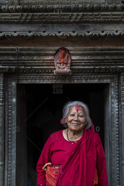 Nuwacot, Nepal - March 30, 2019: A woman in the doorway of a Newari style carved house in the ancient village of Nuwacot