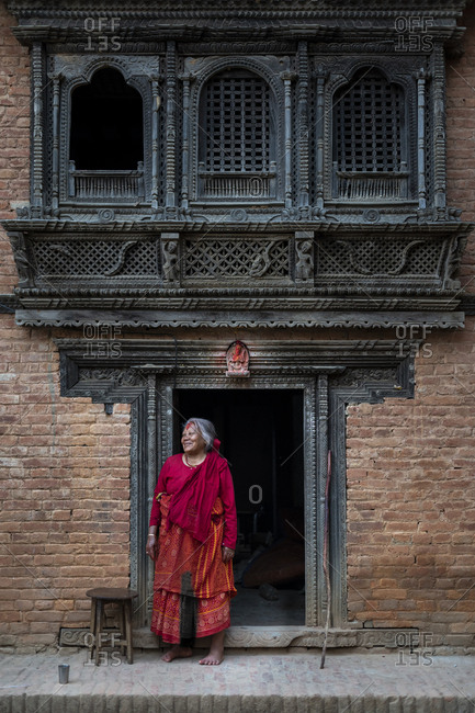 Nuwacot, Nepal - March 30, 2019: A woman standing in the doorway of a Newari style carved house in the ancient village of Nuwacot