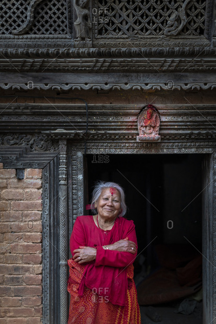 Nuwacot, Nepal - March 30, 2019: Woman standing in the doorway of a Newari style carved house in the ancient village of Nuwacot