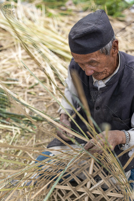 Nepal, Asia - March 31, 2019: Senior Nepali man makes a traditional basket called a Doko by weaving bamboo