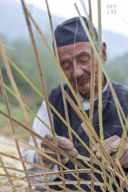 Nepal, Asia - March 31, 2019: A old Nepali man makes a traditional basket called a Doko by weaving bamboo