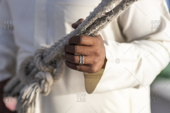 An Egyptian man wearing a ring with an anchor holds rope while sailing a traditional Felucca sailboat on the Nile river