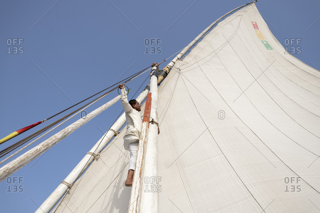 Aswan, Egypt - April 16, 2019: An Egyptian man stands on the bow of a traditional Felucca sailboat with wooden masts and cotton sails on the Nile river