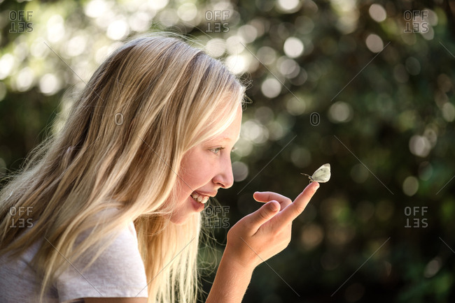 Blonde girl looking at a small moth
